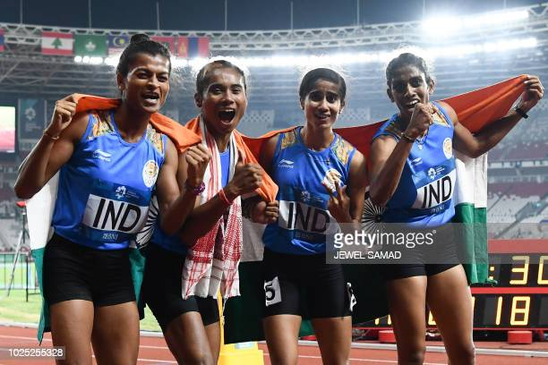 India's athletes celebrate winning the final of the women's 4x400m relay athletics event during the 2018 Asian Games in Jakarta on August 30 2018