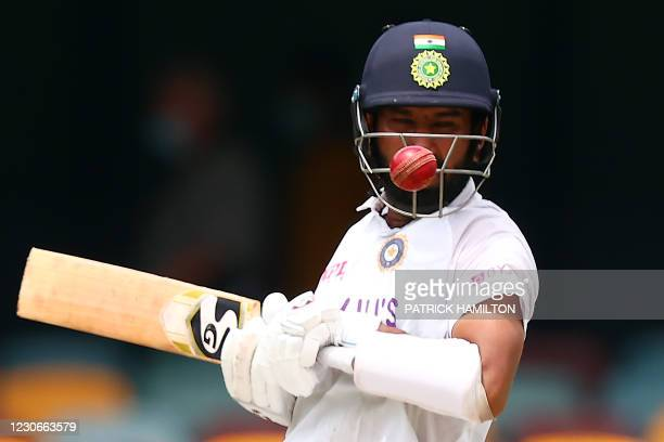 India's batsman Cheteshwar Pujara avoids a bouncer from Australia's paceman Pat Cummins on day five of the fourth cricket Test match between...