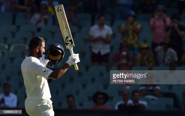 India's batsman Cheteshwar Pujara celebrates his century against Australia during day one of the first cricket Test match at the Adelaide Oval on...