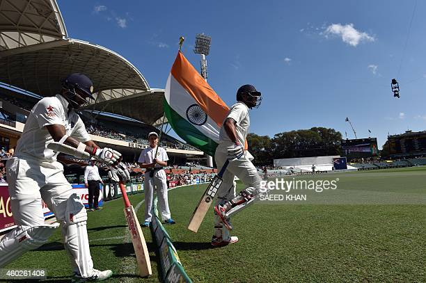 India's batsman Murali Vijay touches the national flag as he enters the grounds with teammate Shikhar Dhawan on the third day of the first Test...