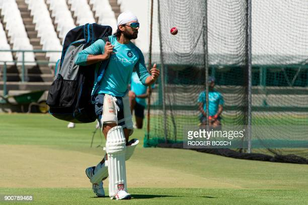 India's batsman Murali Vijay walks across the cricket pitch as he arrives to take part in the Indian cricket team training session at the Newlands...