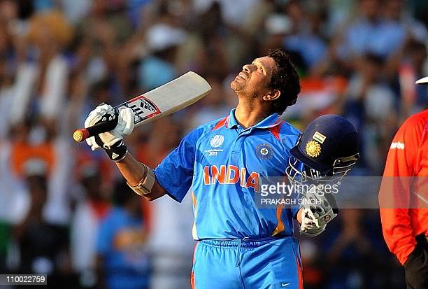 India's batsman Sachin Tendulkar raises his bat and helmet after his century during the Cricket World Cup match between India and South Africa at the...