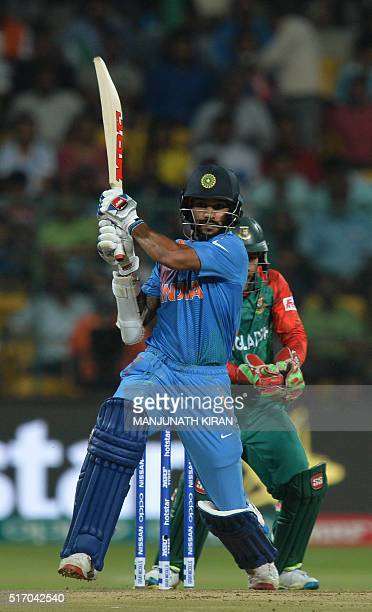 India's batsman Shikhar Dhawan plays a shot during the World T20 cricket tournament match between India and Bangladesh at The Chinnaswamy Stadium in...