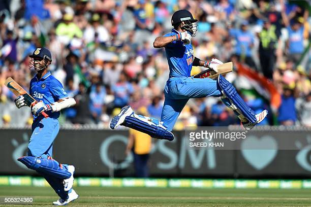 TOPSHOT India's batsman Virat Kohli jumps in the air to celebrates his 100runs against Australia as teammate Ajinkya Rahane complete his run during...