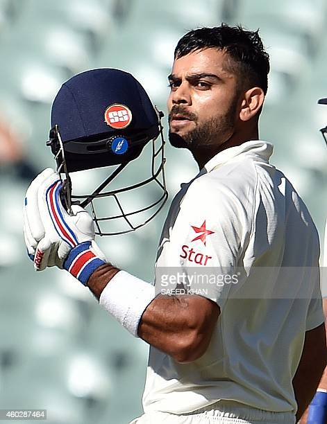 India's batsman Virat Kohli kisses the national flag on his helmet as he celebrates his century during the third day of the first Test cricket match...