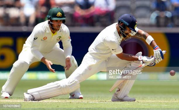 India's batsman Virat Kohli plays a forward defensive shot as Australia's Aaron Finch watches on the third day of the second cricket Test match in...