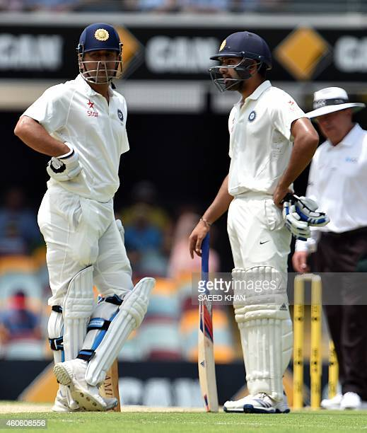 India's batsmen Rohit Sharma and MS Dhoni talks on the second day of the 2nd Test match between Australia and India at The Gabba in Brisbane on...