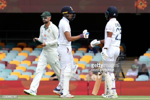 India's batsmen Shubman Gill and Cheteshwar Pujara bumps gloves as Australia's Nathan Lyon walks back to his fielding position on day five of the...