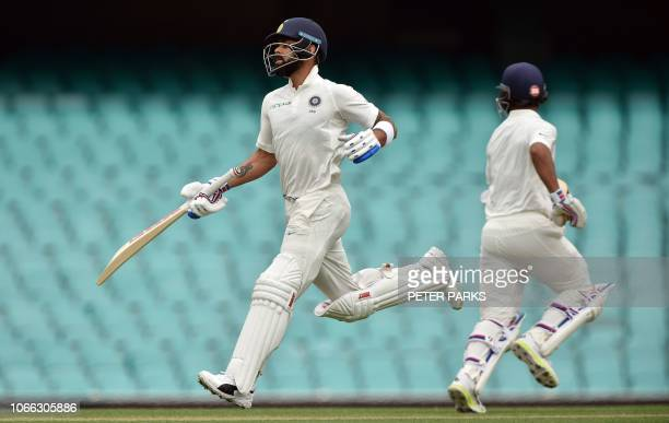 India's batsmen Virat Kohli and Ajinkya Rahane run between the wickets on the second day of the tour match against Cricket Australia XI at the SCG in...