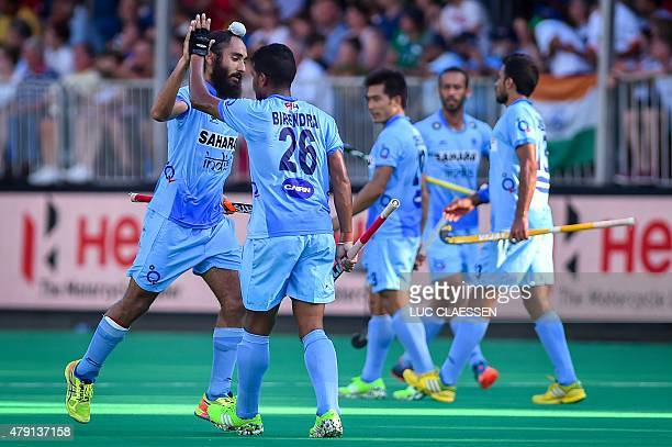 India's Birendra Lakra and India's Sardar Singh celebrate after scoring during the quarterfinal field hockey match between India and Malaysia at the...