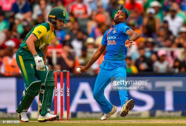 India's bowler Hardik Pandya is watched by South Africa's batsman Farhaan Behardien as he delivers the ball during the first T20I cricket match...