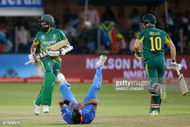 India's bowler Hardik Pandya reacts on the ground as South Africa's batsmen Hashim Amla and David Miller run between the wickets during the fifth one...