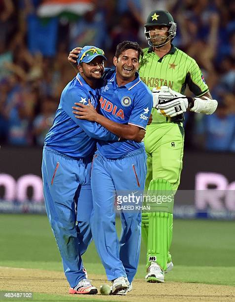 India's bowler Mohit Sharma and fielder Suresh Raina celebrate their victory as Pakistan's batsman Mohammad Irfan leaves the field in the Pool B 2015...