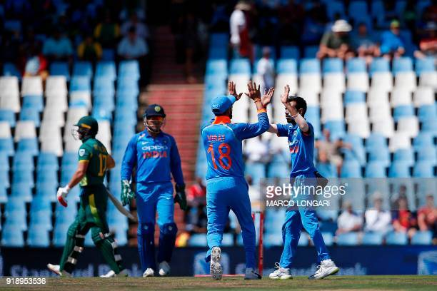 India's bowler Yuzvendra Chahal is celebrated by India's captain Virat Kohli after dismissing South African batsman AB de Villiers during the sixth...