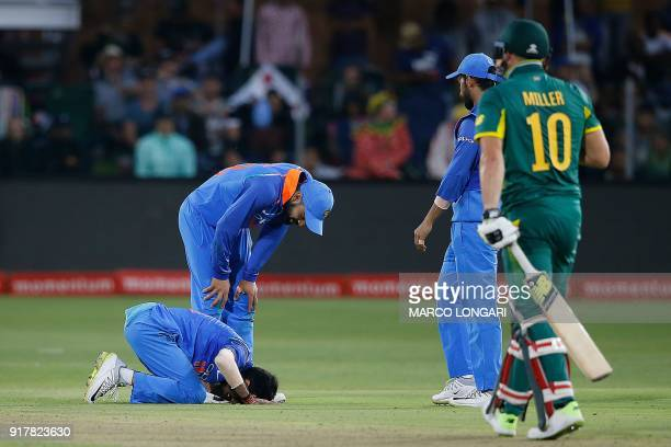India's bowler Yuzvendra Chahal kneels on the pitch as he reacts in pain after being hit in the hand after a shot played by South Africa's batsman...