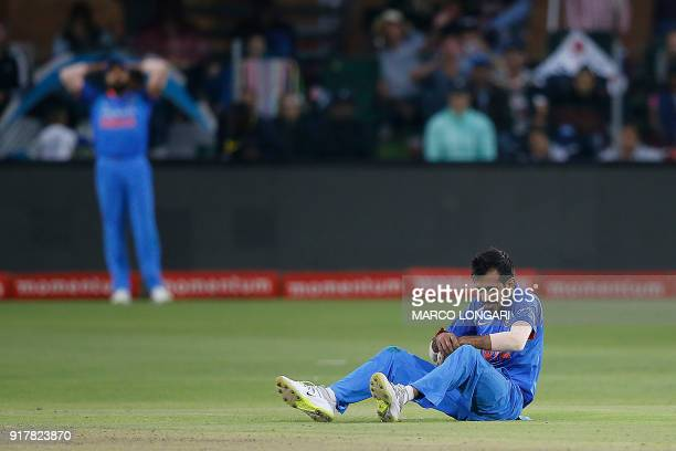 India's bowler Yuzvendra Chahal sits on the pitch as he reacts in pain after being hit in the hand after a shot played by South Africa's batsman...