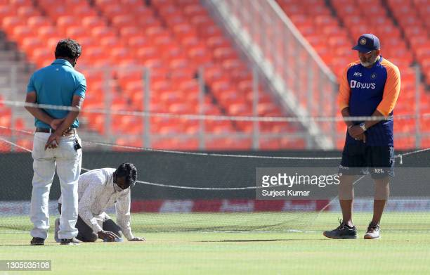 India's bowling coach Bharat Arun looks on as groundsmen work on the pitch during a India Nets Session at Narendra Modi Stadium on March 03, 2021 in...