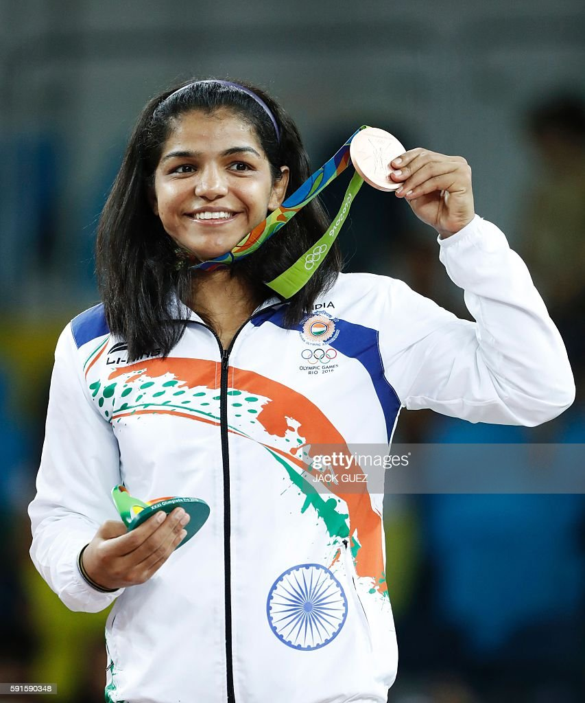 TOPSHOT - India's bronze medallist Sakshi Malik stands on the podium at the end of the women's 58kg freestyle wrestling event at the Carioca Arena 2 in Rio de Janeiro on August 17, 2016, during the Rio 2016 Olympic Games. / AFP / Jack GUEZ