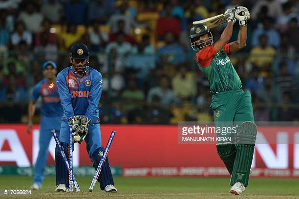 India's captain and wicketkeeper Mahendra Singh Dhoni looks on as Bangladesh's captain Mashrafe Bin Mortaza is bowled during the World T20 cricket...