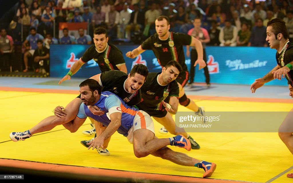India's captain Anup Kumar (bottom) vies with Iran's players during the finals of the Kabaddi World Cup 2016 at the Transstadia in Ahmedabad on October 22, 2016. India defeated Iran 38-29. / AFP / Sam PANTHAKY