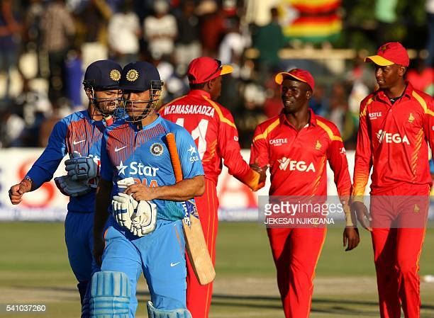 India's captain MS Dhoni leaves the pitch with teammate Rishi Dhawan after defeat during the first T20 cricket match in a series of three games...