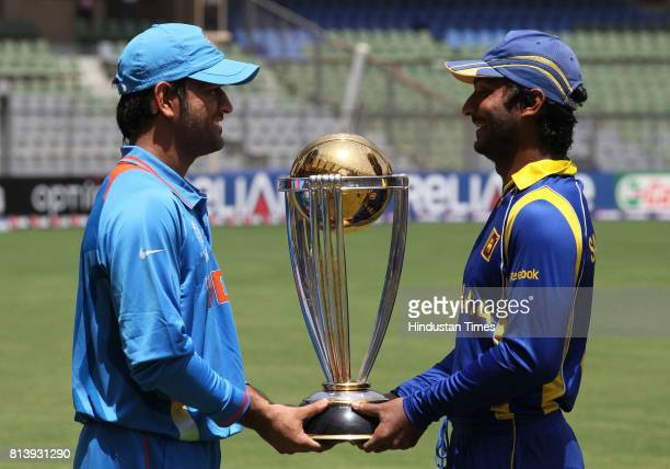 India's captain Mahendra Singh Dhoni and Sri Lanka captain Kumar Sangakkara poses with cricket world cup trophy ahead of their ICC Crciket World Cup...