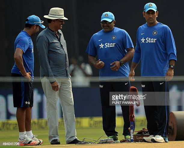 India's captain Mahendra Singh Dhoni looks at the pitch as bowling coach Bharat Arun former cricketer Dilip Vengsarkar and Rohit Sharma look on...