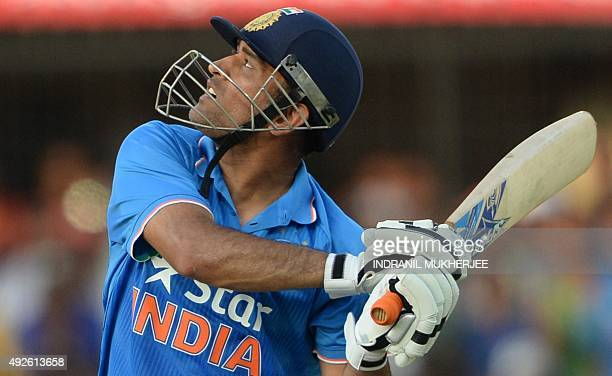 India's captain Mahendra Singh Dhoni looks skywards at the ball after playing a shot during the second one day international cricket match between...