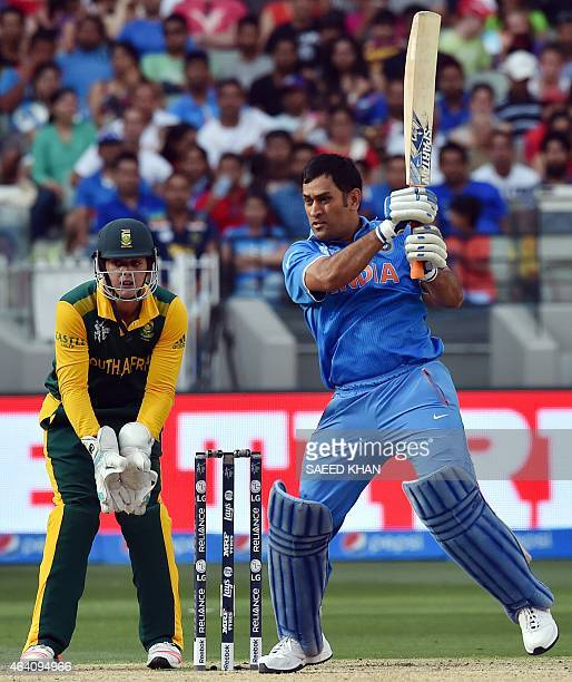 India's captain Mahendra Singh Dhoni plays a shot as South Africa's wicketkeeper Quinton de Kock looks on during the Pool B 2015 Cricket World Cup...