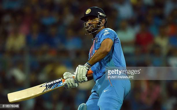 India's captain Mahendra Singh Dhoni plays a shot during the World T20 cricket tournament semifinal match between India and West Indies at The...