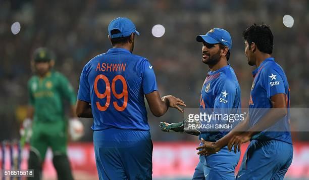 India's captain Mahendra Singh Dhonicelebrates with teammates Ravichandran Ashwinand Jasprit Bumrahafter Ashwin took a catch to dismiss Pakistan...
