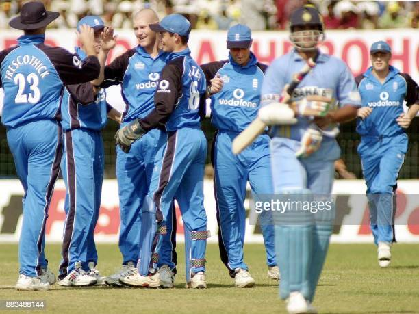 India's captain Sourav Ganguly walks off the pitch as England's bowler Matthew Hoggard is congrtulated by teammates Marcus Trescothick James Foster...