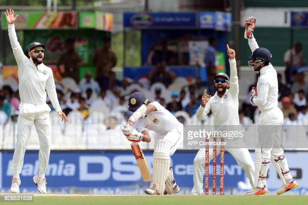 India's captain Virat Kohli and his teammates Ajinkya Rahane and wicketkeeper Wriddhiman Saha unsuccessfully appeal for a Leg Before Wicket decision...