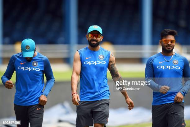 India's captain Virat Kohli and his teammates Ravindra Jadeja and Rishabh Pant warm up during a practice session at the Queen's Park Oval in Port of...