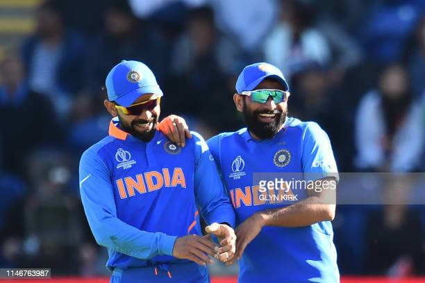 India's captain Virat Kohli and India's Mohammed Shami have a laugh duting the drinks break during the 2019 Cricket World Cup warm up match between...