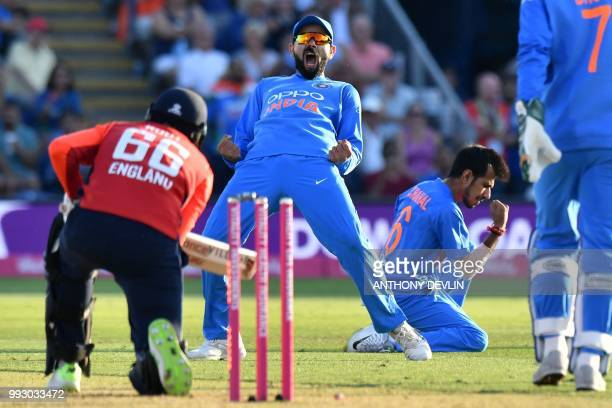 India's captain Virat Kohli and India's Yuzvendra Chahal celebrate after Chahal bowls England's Joe Root during the international Twenty20 cricket...