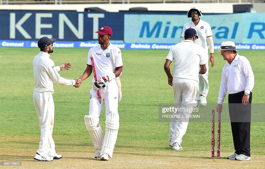 India's captain Virat Kohli and Roston Chase of the West Indies congratulate one another at the end of their match on day five of their Second Test cricket match on August 3, 2016 at Sabina Park in Kingston, Jamaica which ended in a draw. / AFP / Frederic J. BROWN