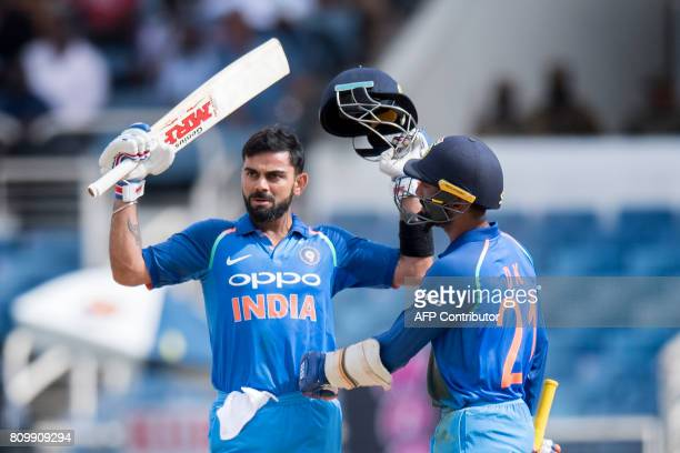 India's Captain Virat Kohli celebrates his century with teammate Dinesh Karthik during the fifth One Day International match between West Indies and...