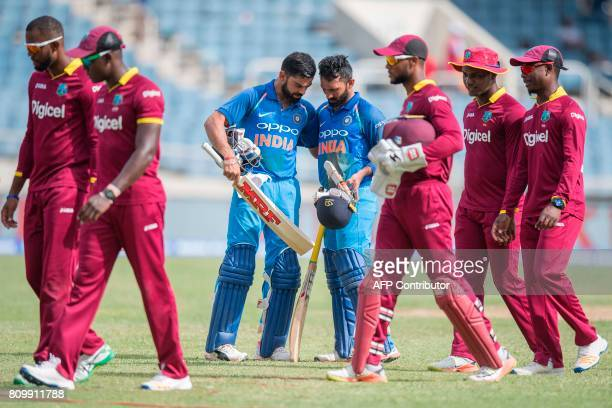 India's Captain Virat Kohli celebrates their victory with teammate Dinesh Karthik during the fifth One Day International match between West Indies...