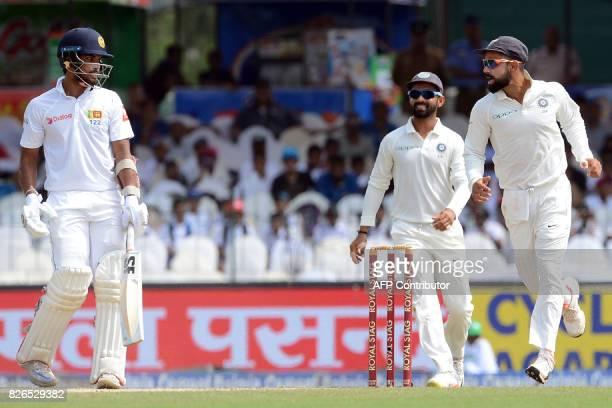 India's captain Virat Kohli celebrates with his teammate Ajinkya Rahane after Sri Lanka's captain Dinesh Chandimal was dismissed during the third day...