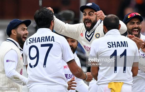 India's captain Virat Kohli celebrates with India's Ishant Sharma and teammates after the successful appeal for the wicket of England's Jonny...