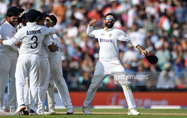 India's captain Virat Kohli celebrates with teammates after England's Chris Woakes was dismissed during play on the fifth day of the fourth cricket...