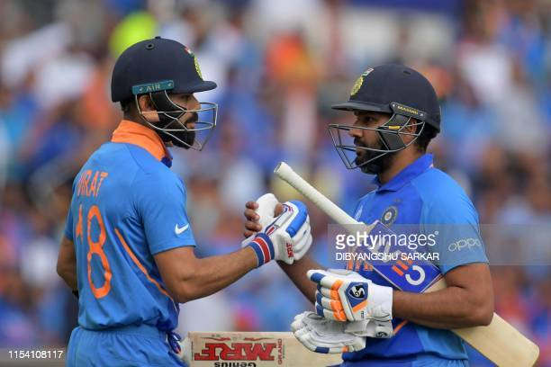 India's captain Virat Kohli congratulates India's Rohit Sharma as he passes him on his way back to the pavilion after losing his wicket for 103...