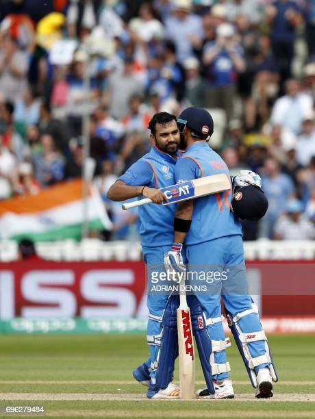 India's captain Virat Kohli congratulates Rohit Sharma on reaching 100 during the ICC Champions Trophy semifinal cricket match between India and...