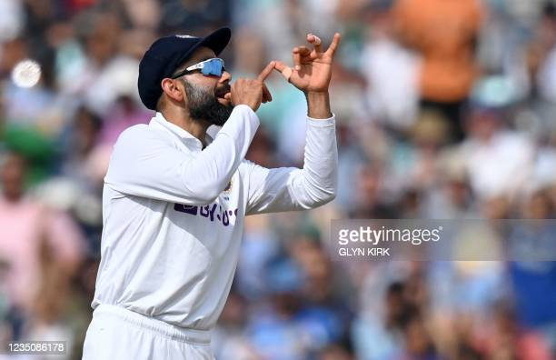 India's captain Virat Kohli gestures towards a trumpet-playing England fan during play on the fifth day of the fourth cricket Test match between...