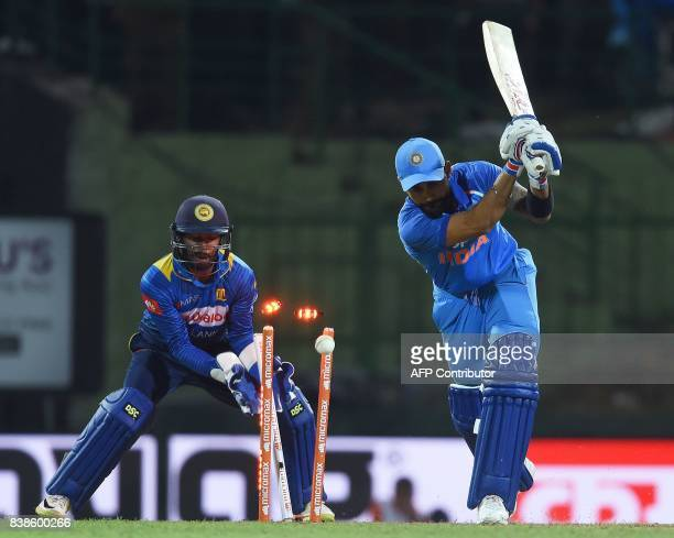 India's captain Virat Kohli is dismissed as Sri Lanka's wicketkeeper Niroshan Dickwella looks on during the second One Day International cricket...