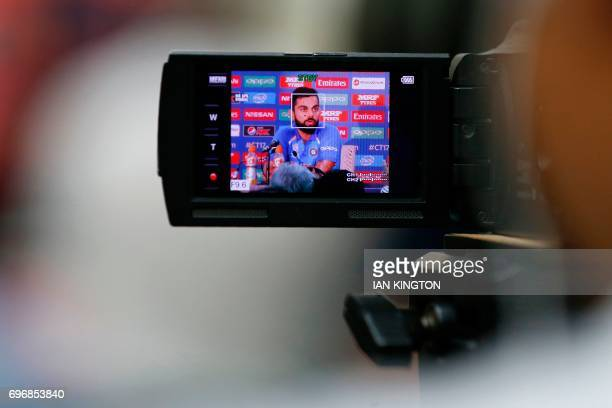 India's captain Virat Kohli is pictured on the monitor of a television camera as he speaks during a press conference folling a nets practice session...