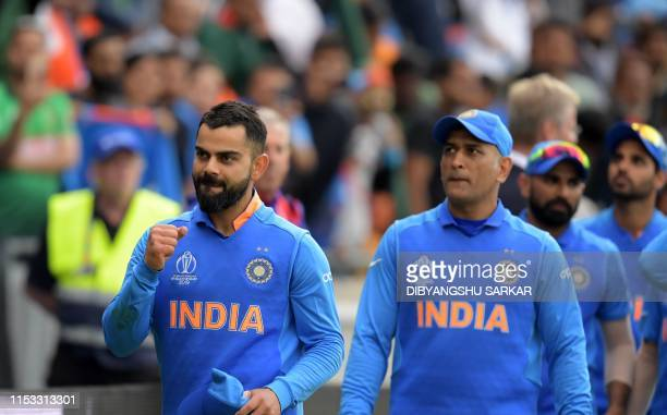 India's captain Virat Kohli leads his team as they celebrate after victory in the 2019 Cricket World Cup group stage match between Bangladesh and...