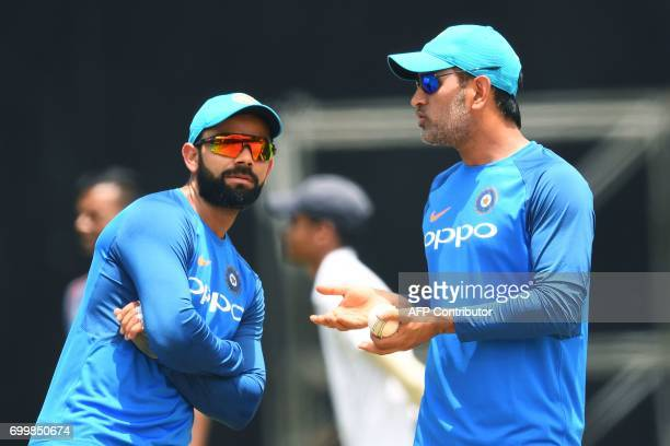 India's captain Virat Kohli listens to teammate MS Dhoni during a practice session at the Queen's Park Oval in Port of Spain Trinidad on June 22...