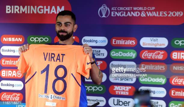 India's captain Virat Kohli poses with his new team colours during a press conference at Edgbaston in Birmingham central England on June 29 ahead of...